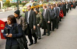 Demandeurs d'emploi américains faisant la queue devant une agence pour l'emploi à New York.