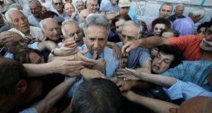 Un employé de la Banque Nationale de Grecque distribue des billets prioritaires pour les retraités faisant la queue devant une succursale bancaire dans le centre d'Athènes.